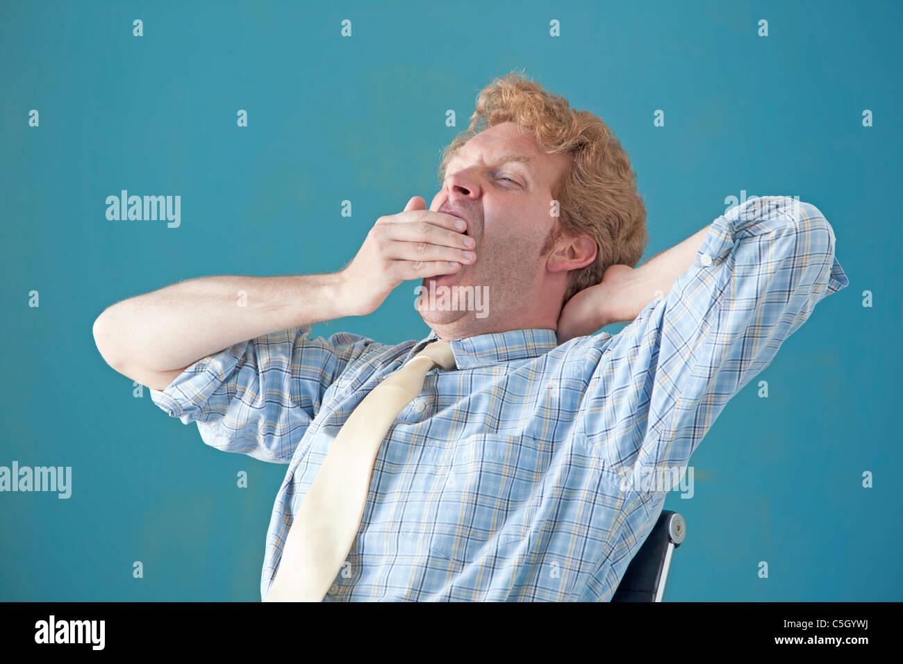 man yawning while sitting - Stock Image