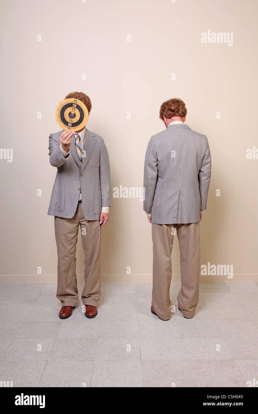two men hiding faces, one behind a target, the other with back - Stock Image