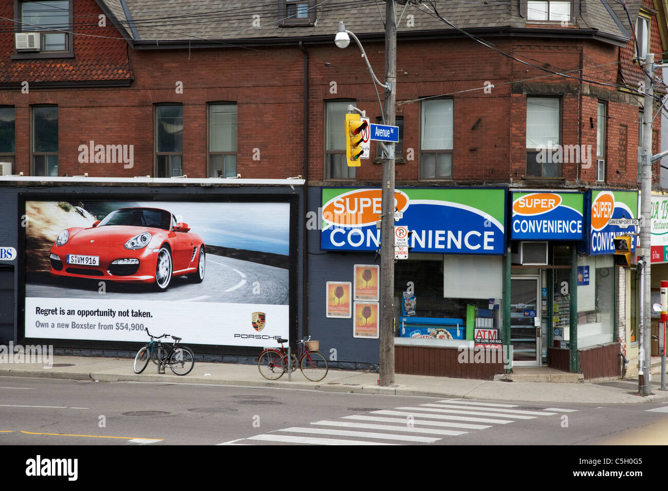 contrasting ad for exclusive luxury car next to corner convenience store toronto ontario canada - Stock Image