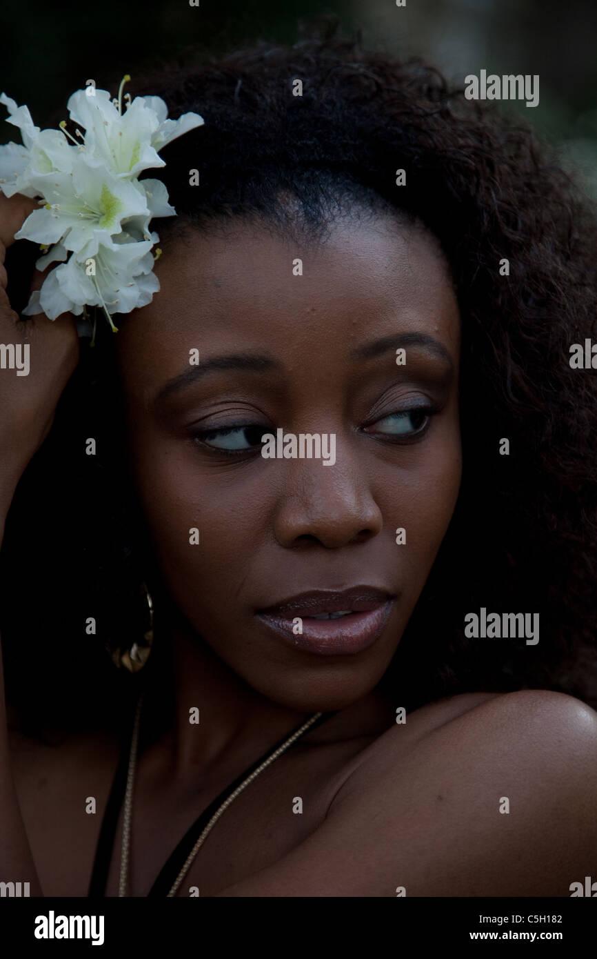 Lovely black woman putting white flowers in her hair and looking to lovely black woman putting white flowers in her hair and looking to the right mightylinksfo