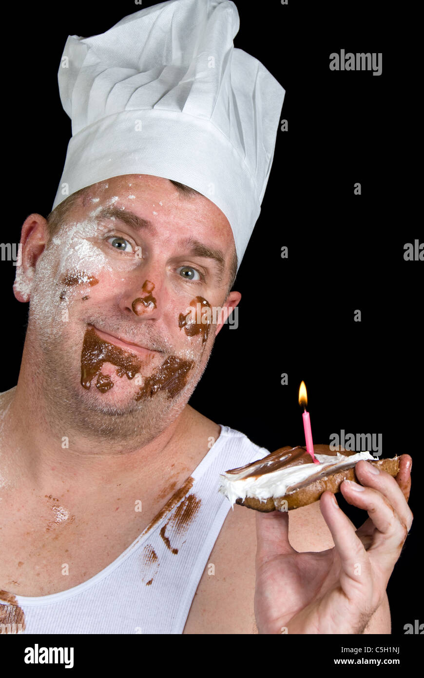 A chef shows off his failed cake consisting of a piece of burnt toast, with chocolate and vanilla icing and a birthday - Stock Image
