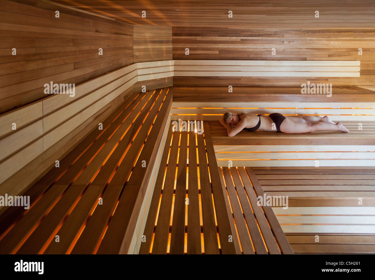 Young woman relaxes in a dry sauna in a spa in Quebec, Canada - Stock Image