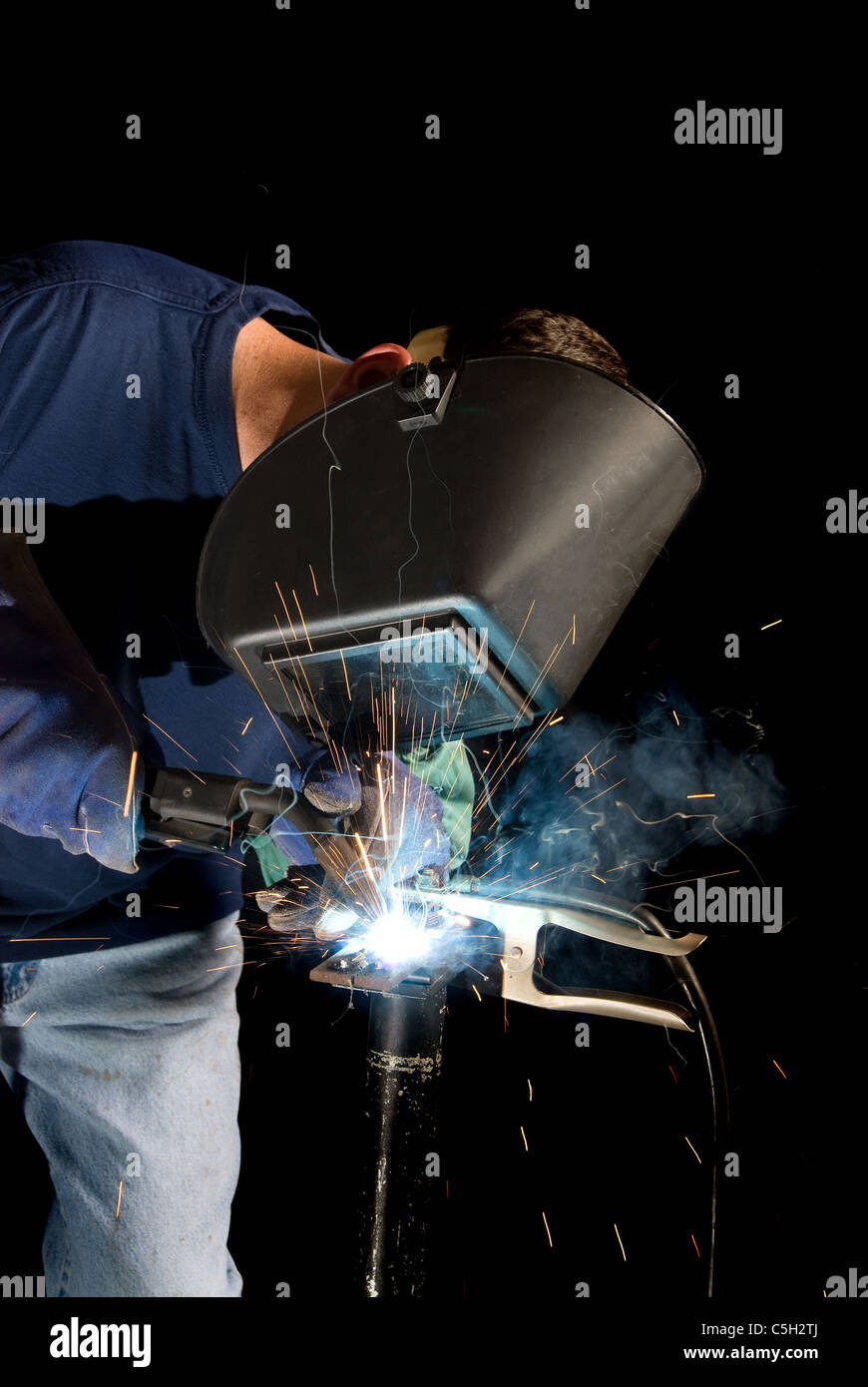 A welder fabricates a tool by attaching two pieces of metal. - Stock Image