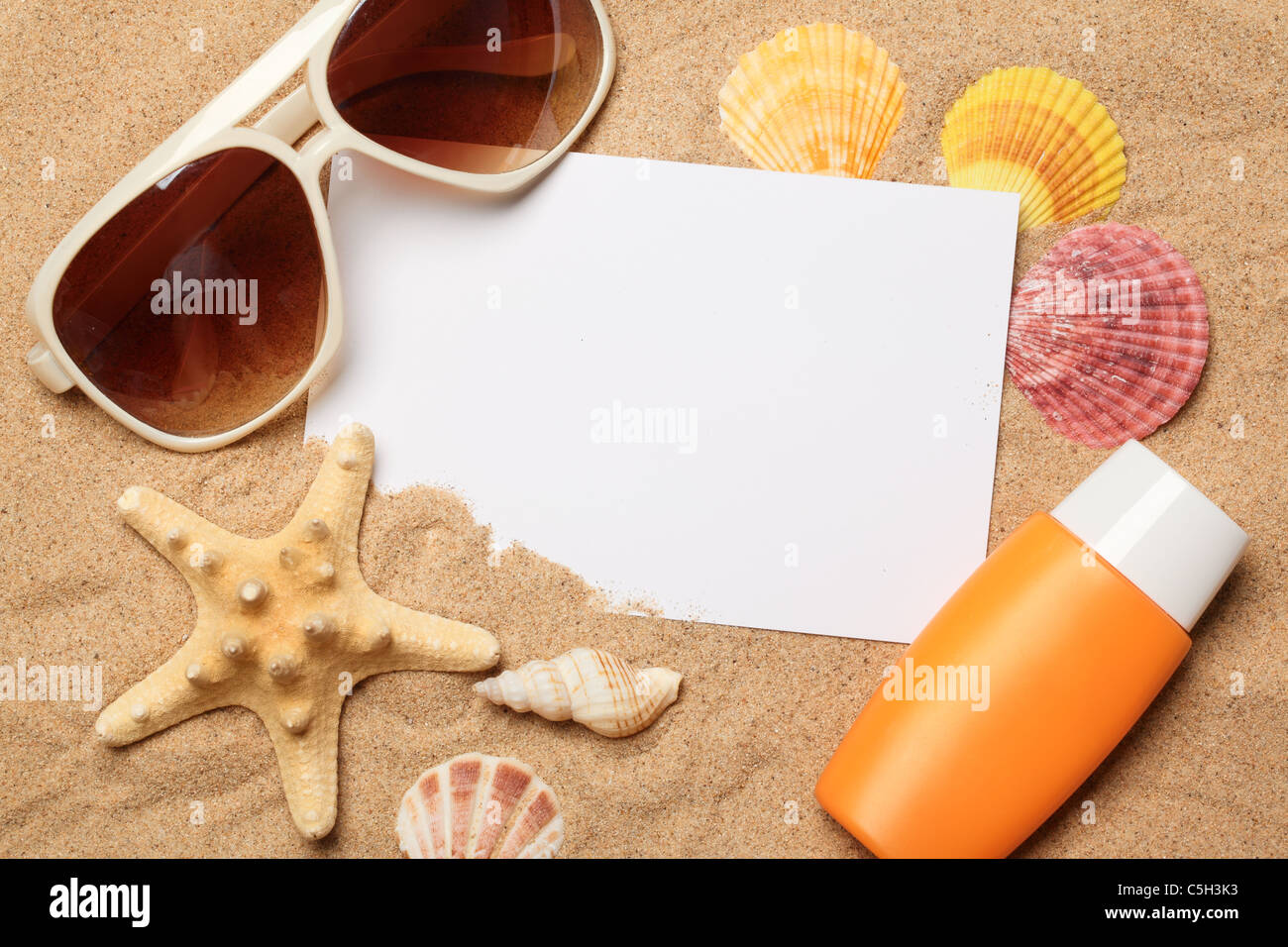 Sunglasses,sunblock and seashells with a blank card on sand. - Stock Image
