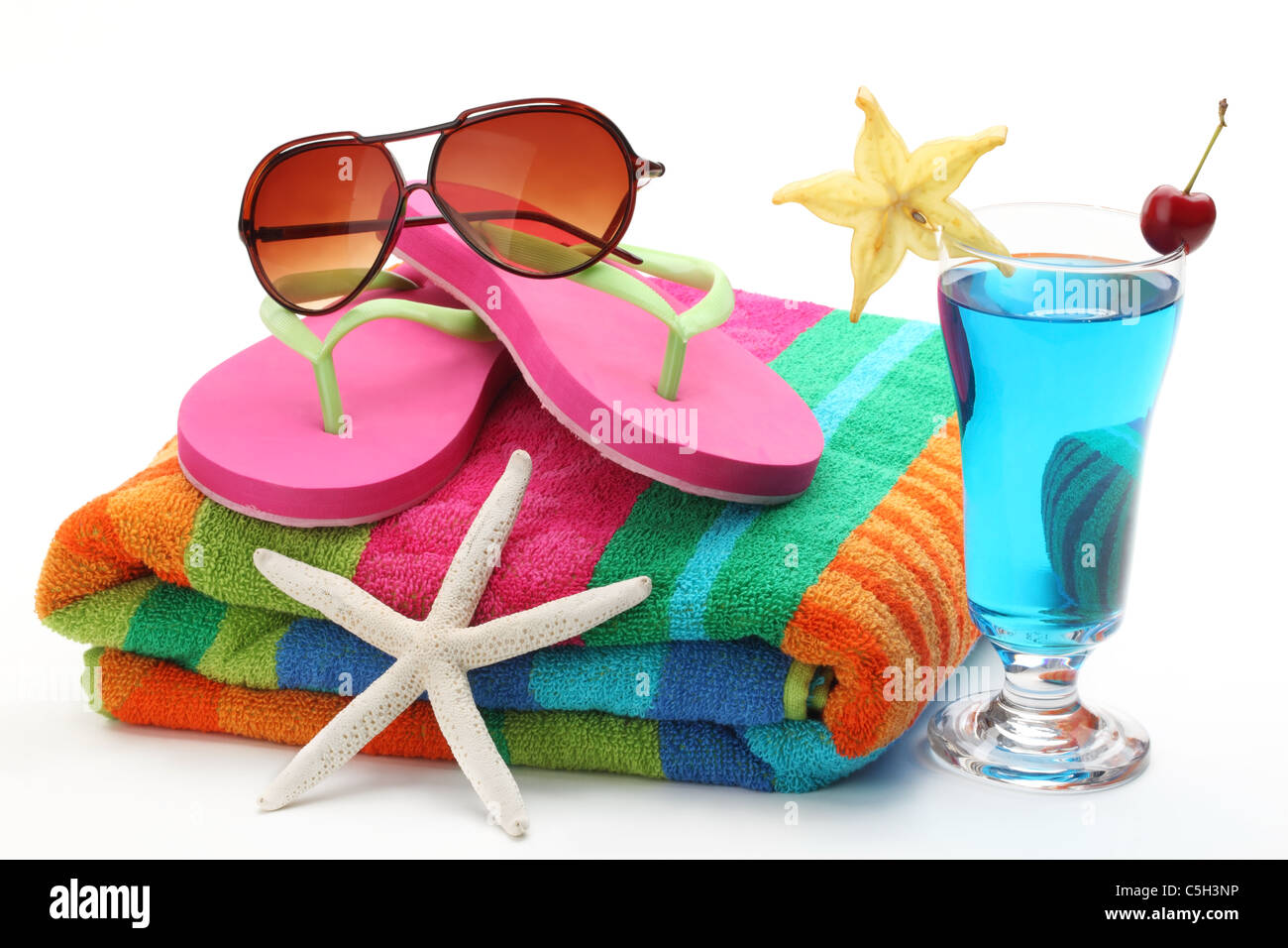 Beach items with towel,flip flops, sunglasses and a glass of cocktail.Isolated on white background. - Stock Image