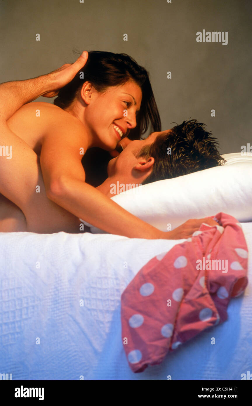 Couple playing in bed nude, happy and romantic