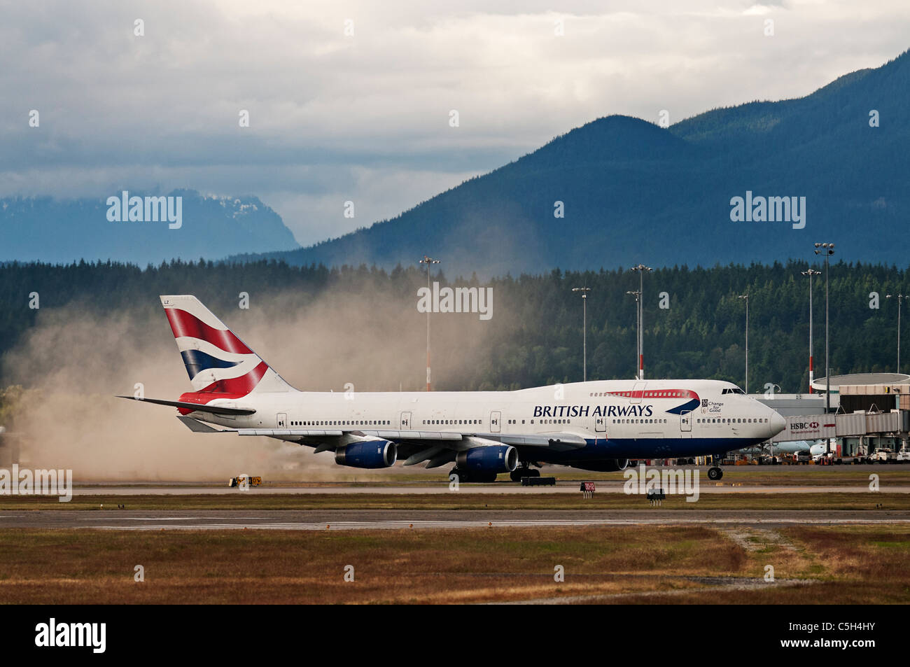The jet engine thrust from a British Airways Boeing 747 kicks up a small dust storm as it taxies along the tarmac. - Stock Image