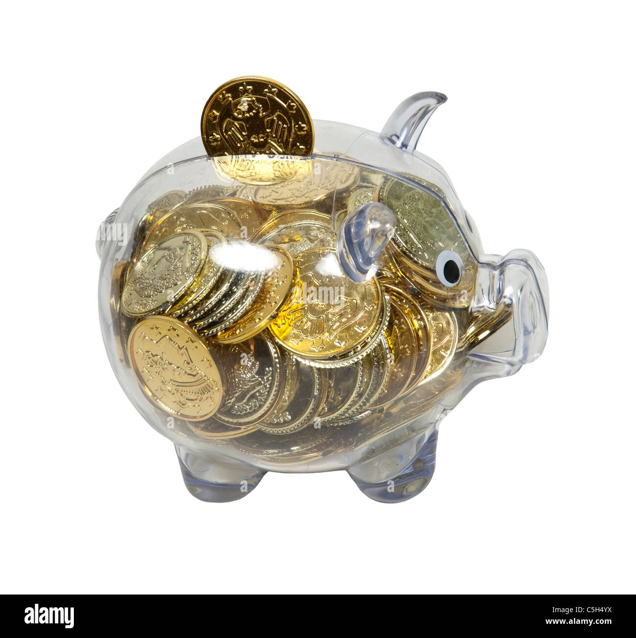 Piggy bank used to save change for a future purchase filled with gold coins - path included - Stock Image