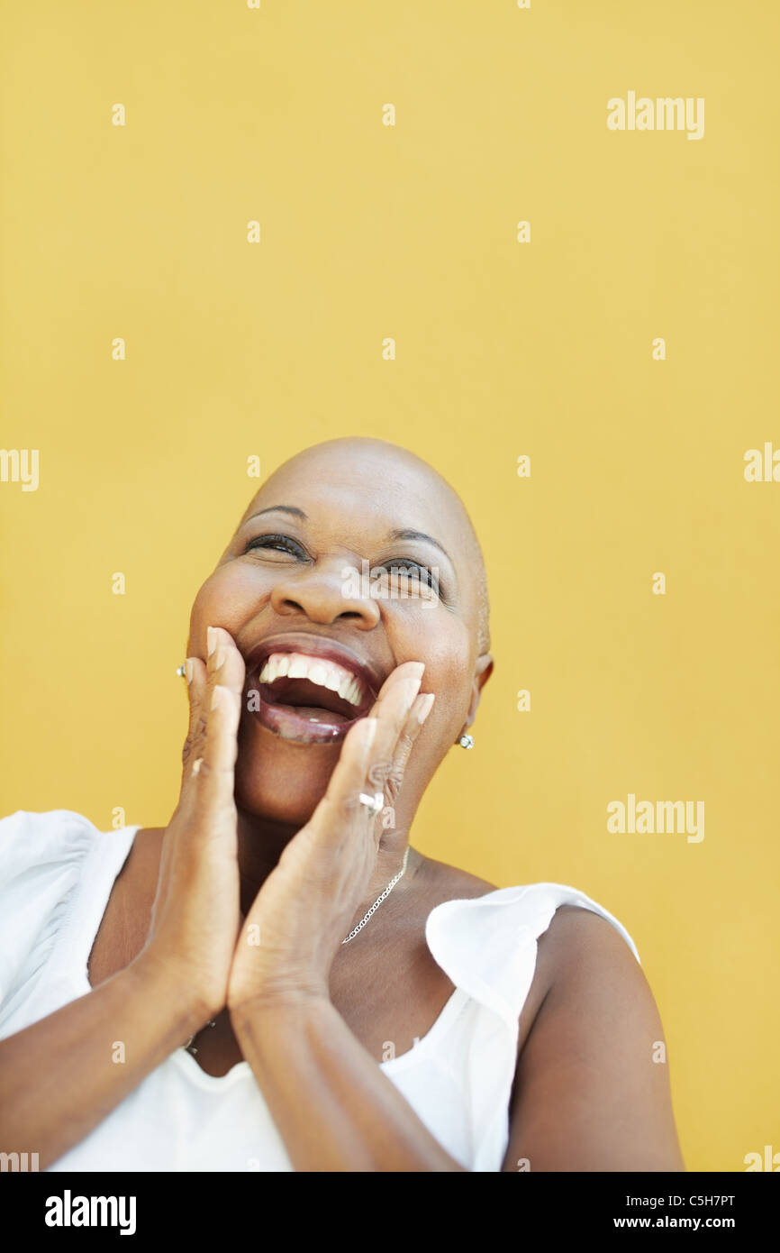 portrait of african 50 years old surprised woman with bald head, smiling on yellow background. Head and shoulders, - Stock Image