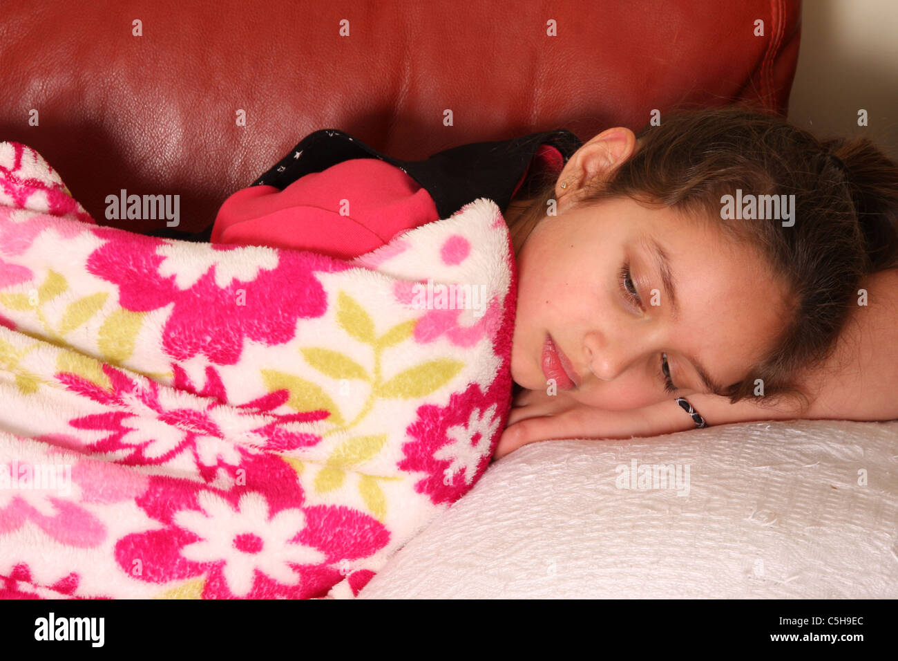 A twelve year old girl feeling sick and resting under a blanket on her sofa. - Stock Image