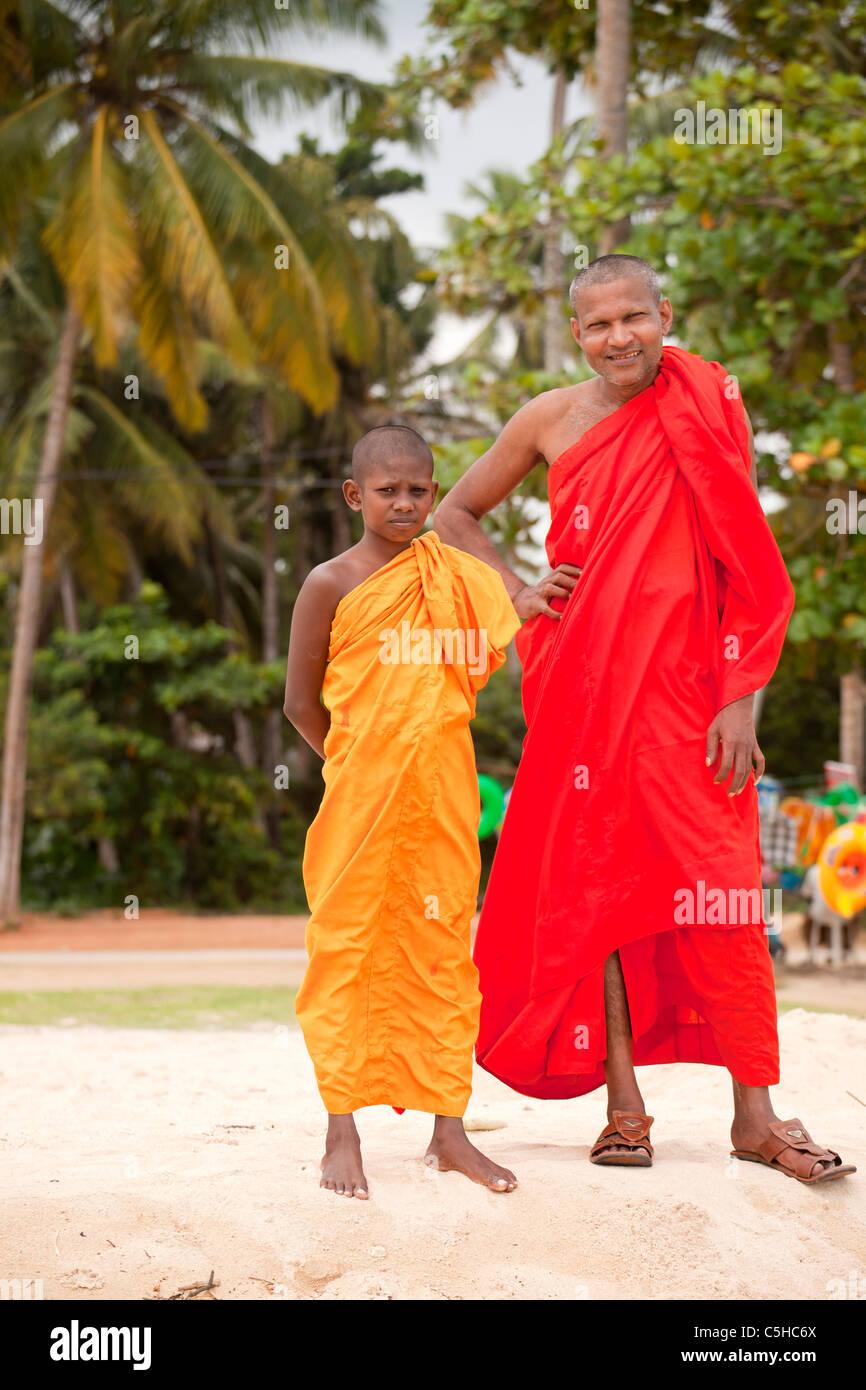 buddhist monk and novice in typical orange robe at the beach in Polhena, Matara, LKA, Sri Lanka - Stock Image