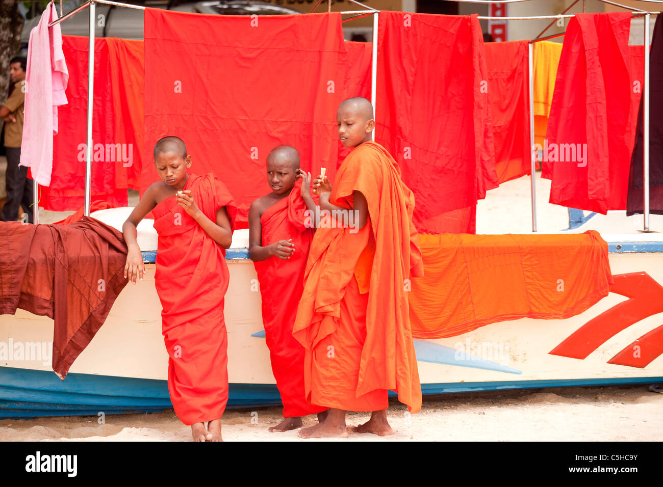 buddhist novices in typical orange robe and their clothes line at the beach in Polhena, Matara, LKA, Sri Lanka - Stock Image