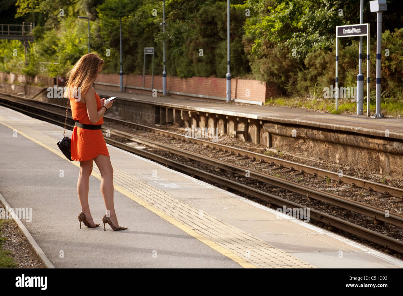 Young woman waiting for a train, Elmstead Woods station, Southeastern trains, London UK - Stock Image