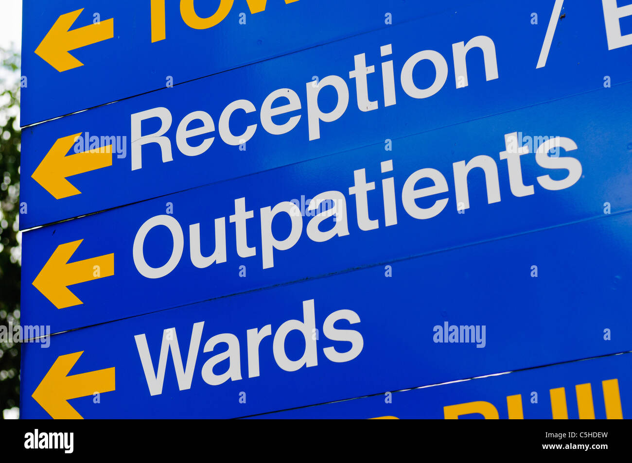 Sign in a hospital directing visitors to reception, outpatients and wards. - Stock Image