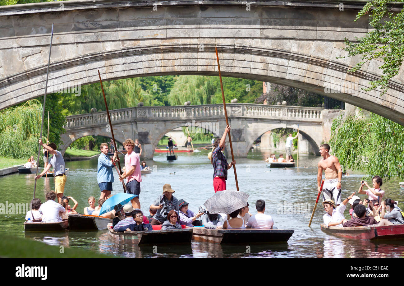 Chauffeur punts with tourists aboard on the River Cam looking through Kings College Bridge to Clare College Bridge - Stock Image