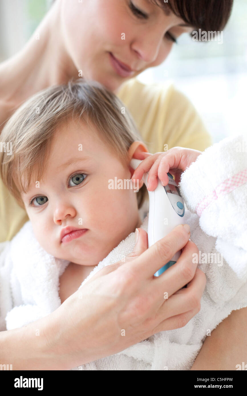Taking a toddler's temperature - Stock Image