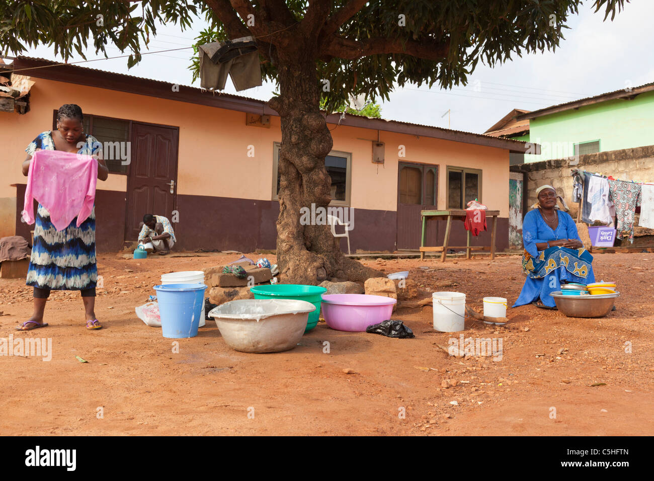 Two African Women Washing Clothes By Hand In Buckets Accra Ghana