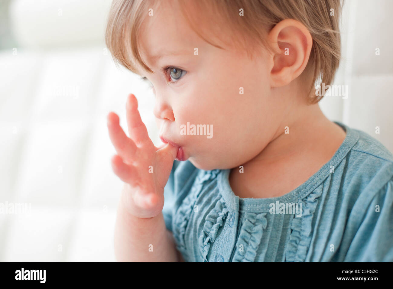 Toddler sucking her thumb - Stock Image
