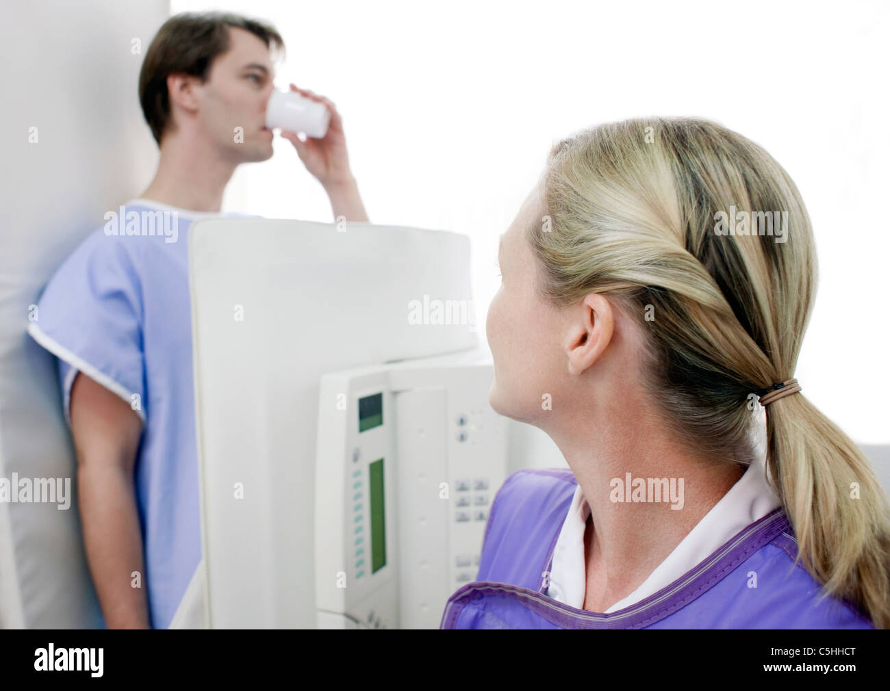 Man swallowing barium during an X-ray - Stock Image