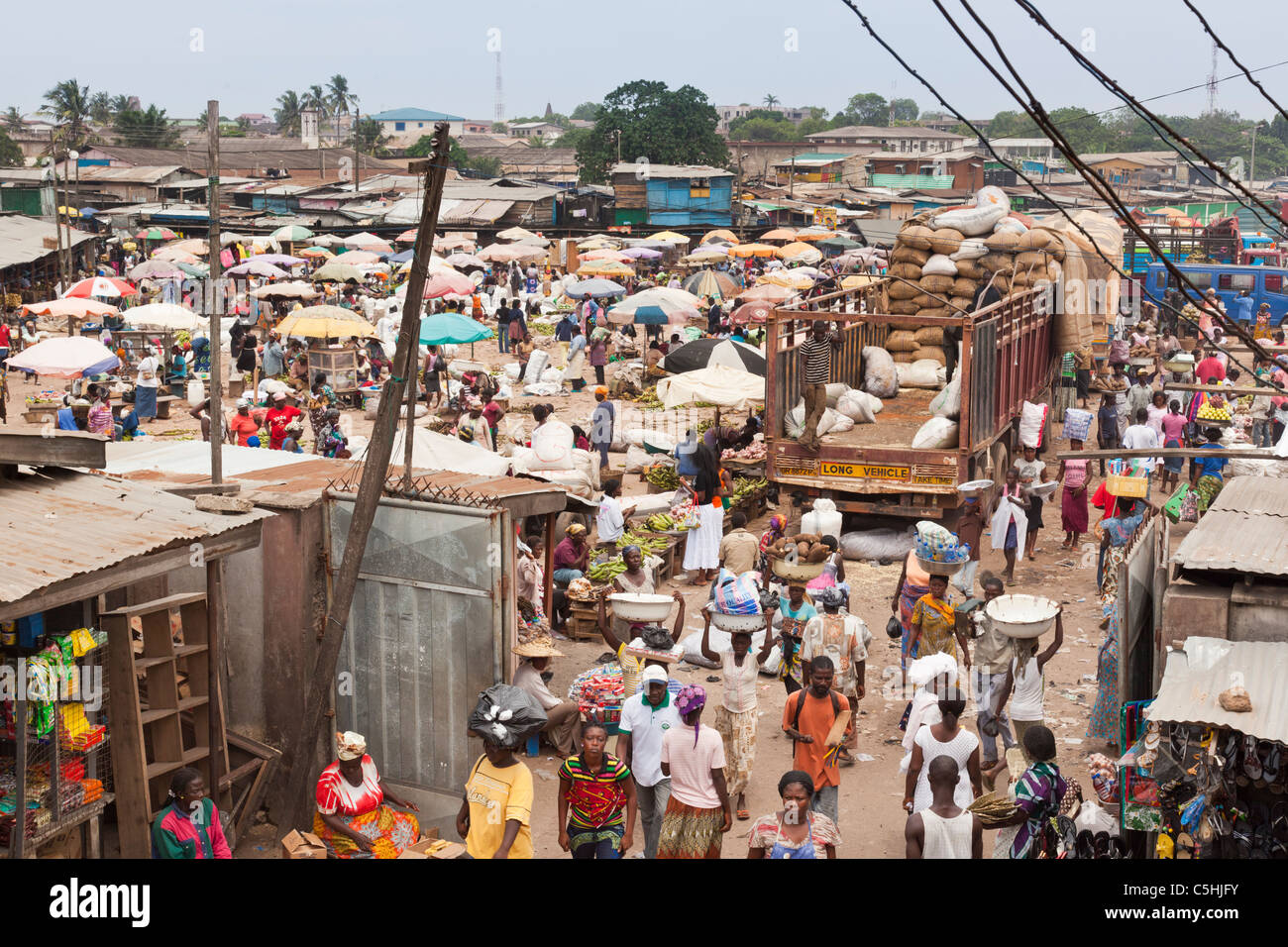 Sacks of coco beans being unloaded from an articulated trailer in a typical market scene. Agbogbloshie Market, Accra, - Stock Image