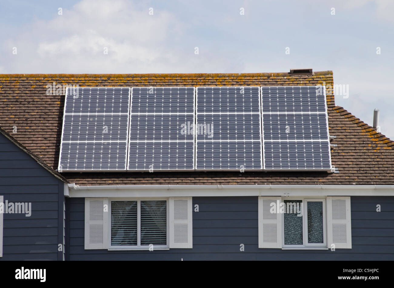 Twelve photovoltaic solar panels on an energy efficient eco home house roof residential domestic property. West - Stock Image