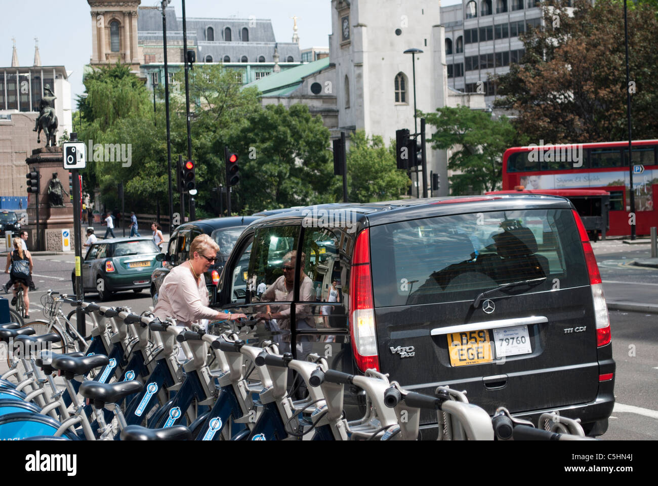 Person getting into a taxi next to a rack of Barclays Bank Cycle Hire bicycles at a docking station in the City - Stock Image
