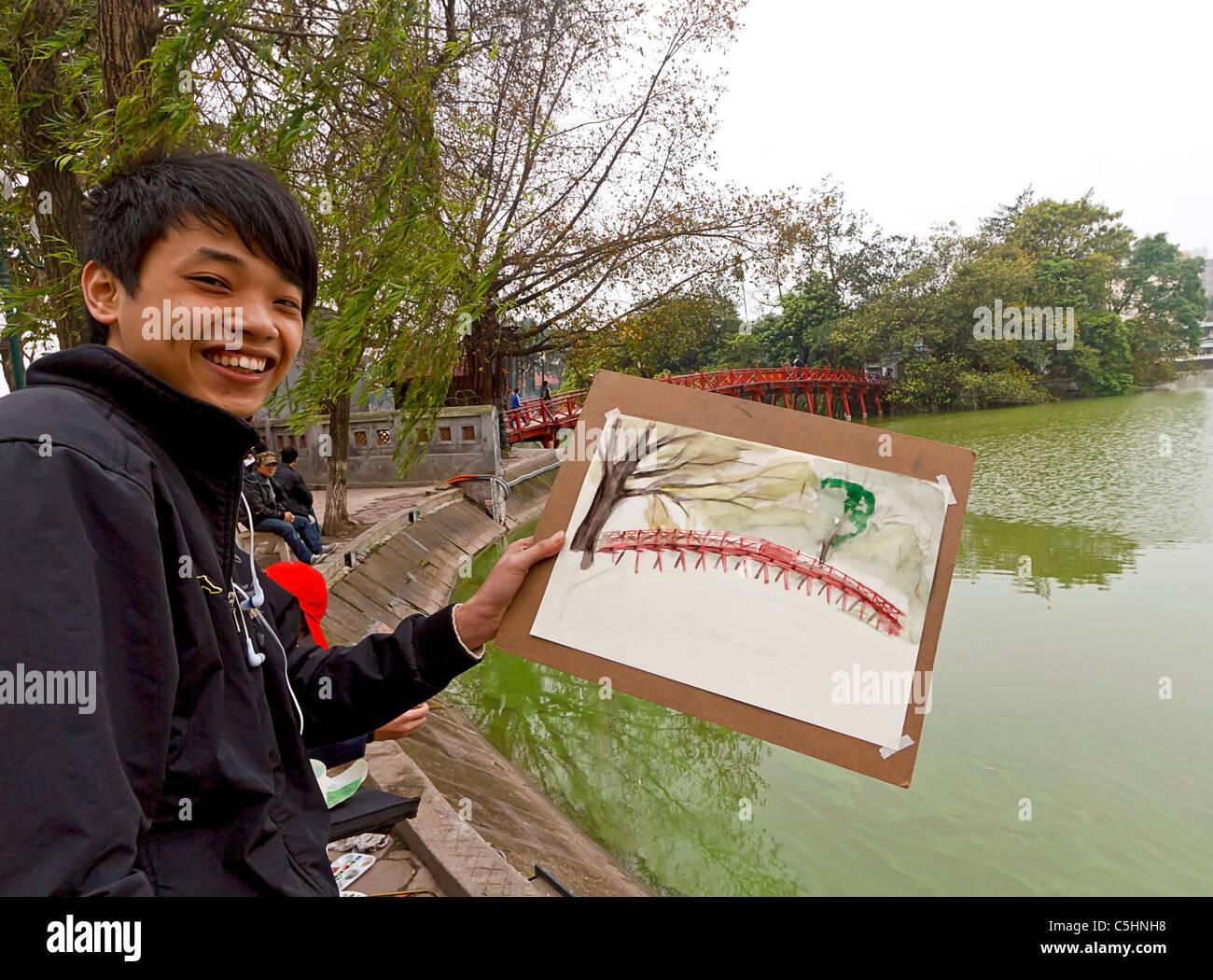 Local young men paint popular red bridge over Hoan Kiem Lake in the historical center of Hanoi, Vietnam. - Stock Image