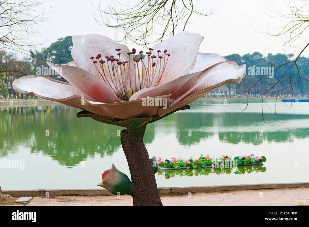 Large statue of lotus flower (with real lotus flowers on a floating planter in the background) in front of Hoan - Stock Image