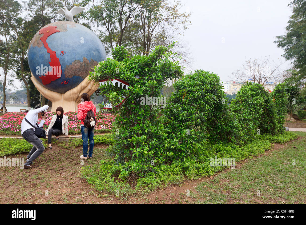 Dragon topiary sits by globe of the world in front of Hoan Kiem Lake in the historical center of Hanoi, Vietnam. - Stock Image