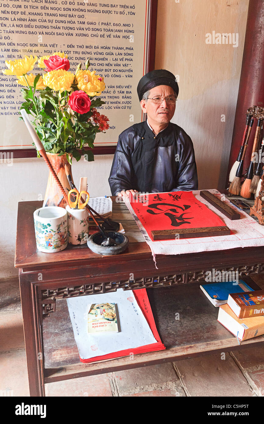Man does calligraphy in Ngoc Son Pagoda (Temple of the Jade Mound), Buddhist temple at Hoan Kiem Lake, Hanoi - Stock Image