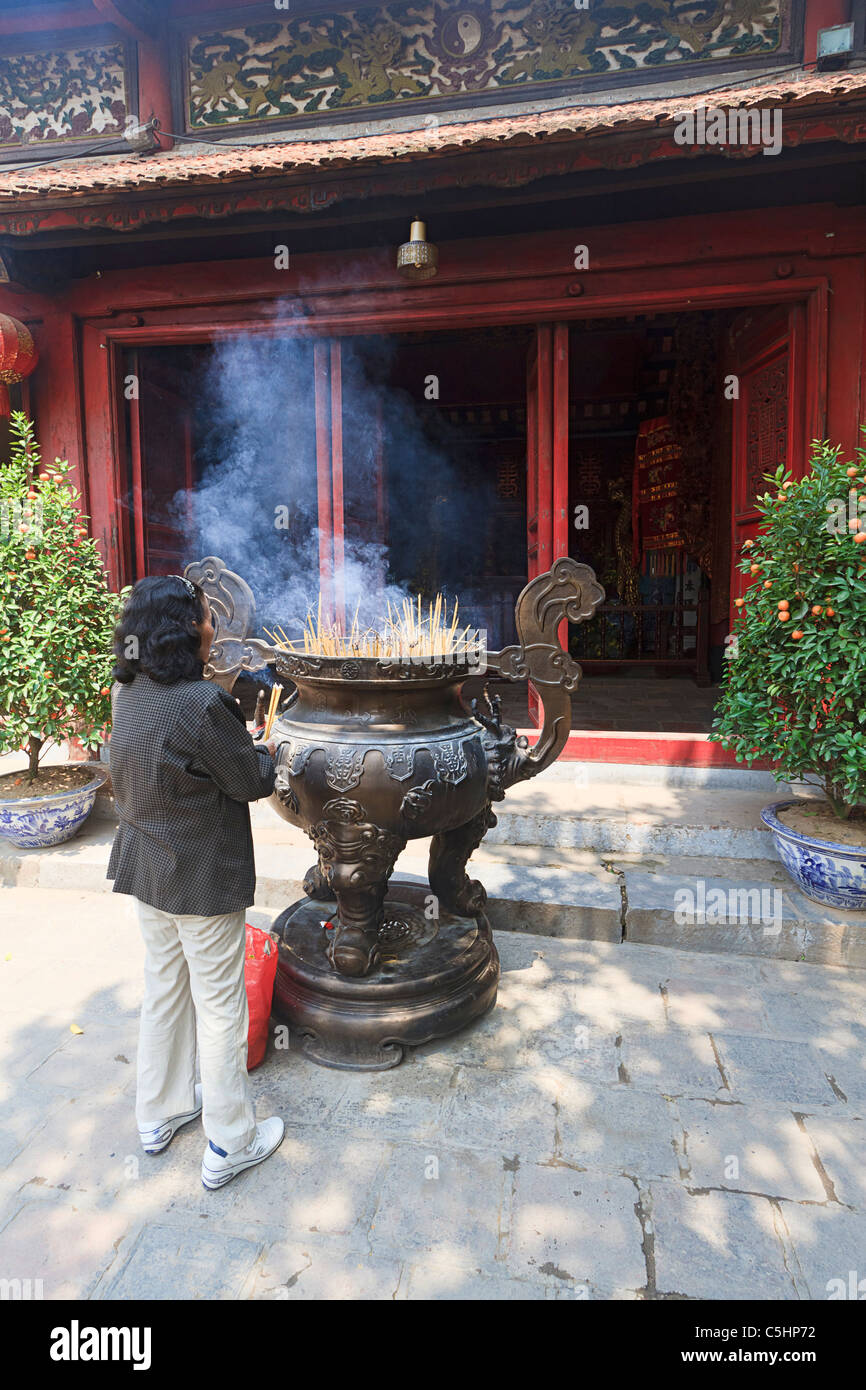 Woman lights incense offering at Ngoc Son Pagoda (Temple of the Jade Mound), Buddhist temple on island on Hoan Kiem - Stock Image
