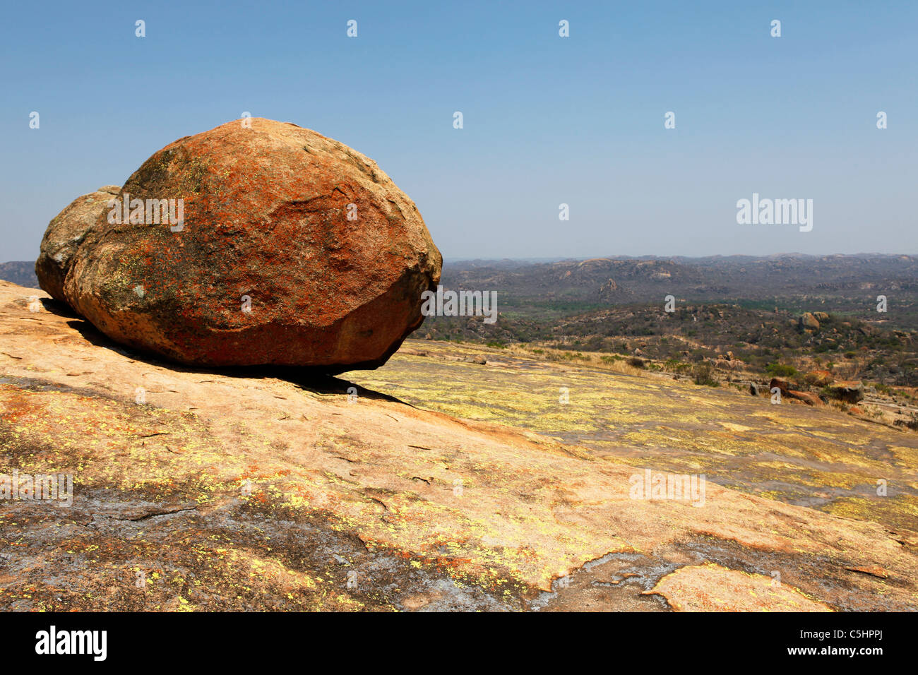 A boulder lies on a hillside in the Rhodes-Matopos National Park close to Bulawayo, Zimbabwe. - Stock Image