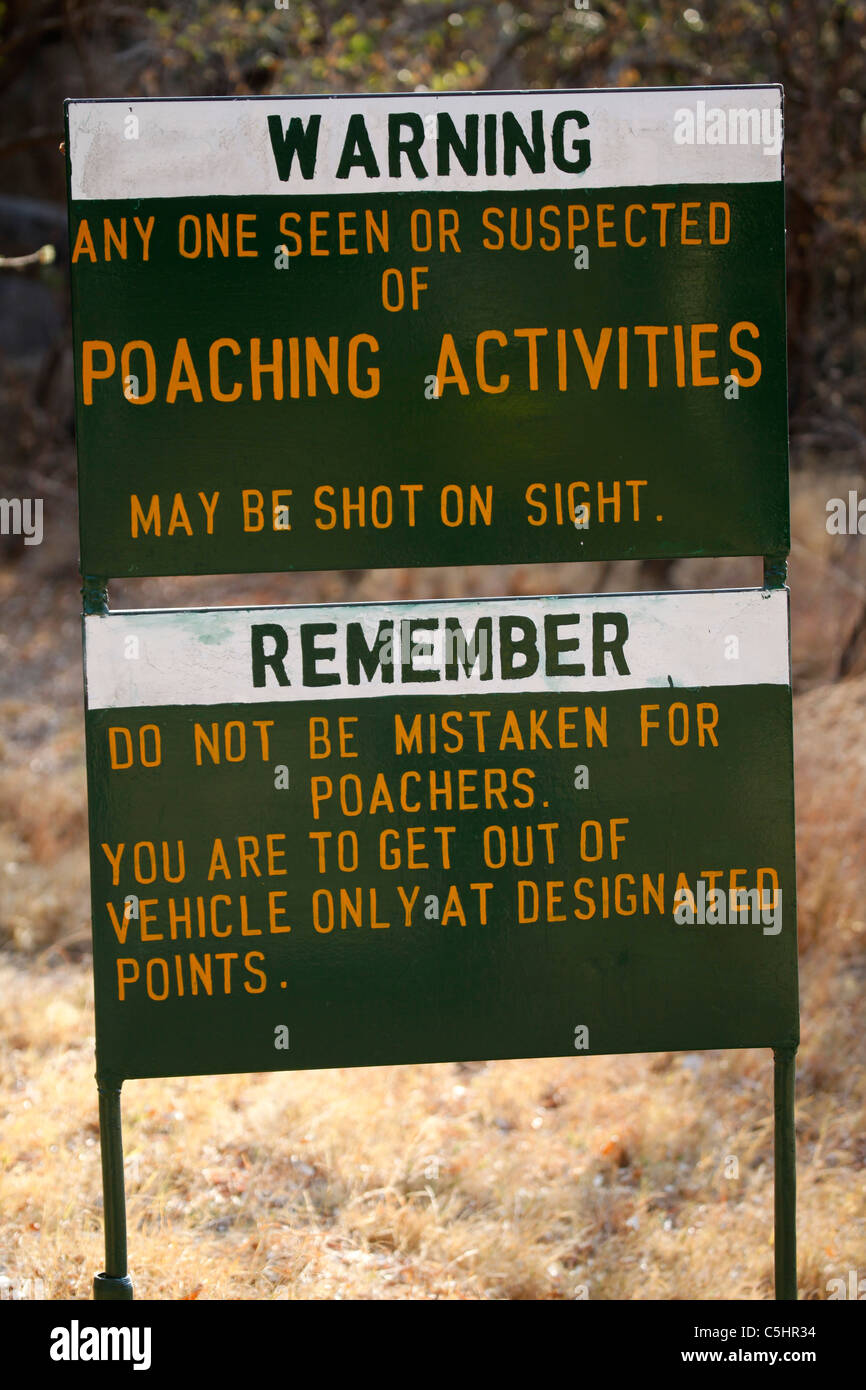A sign warns that poachers can be shot on sight in the Rhodes-Matopos National Park, close to Bulawayo, Zimbabwe. - Stock Image