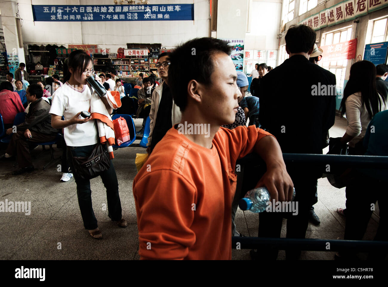 young migrant worker buying a bus ticket to return to his village,guyuan,ningxia province, china - Stock Image