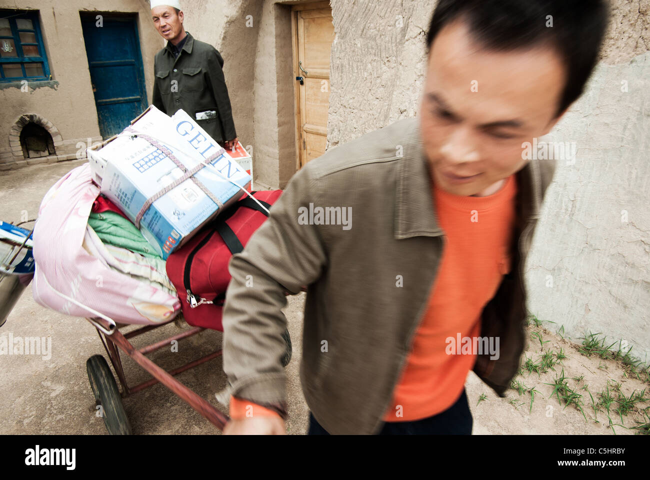 migrant worker leaving his home to look for work, father in background, china, ningxia province - Stock Image