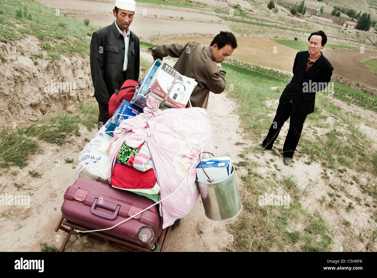 migrant worker being stopped by government officials upon departure to the city, china, ningxia province - Stock Image
