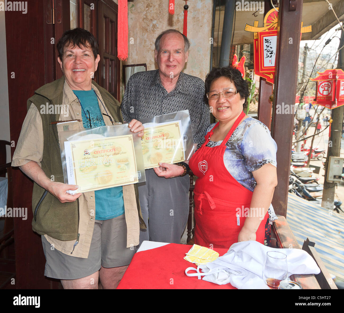 Man and woman  'graduate' from cooking class at Cafe Anh Tuyet in Hanoi, Vietnam, taught by celebrity chef - Stock Image
