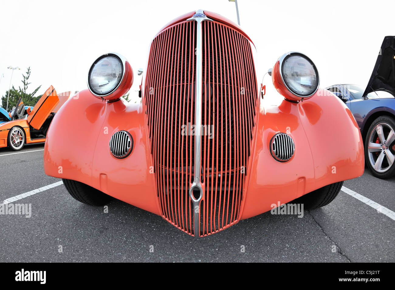 Antique Car, orange Ford with front tall chrome grille, headlamps, seen from ground level, Custom Classic Car Meet - Stock Image