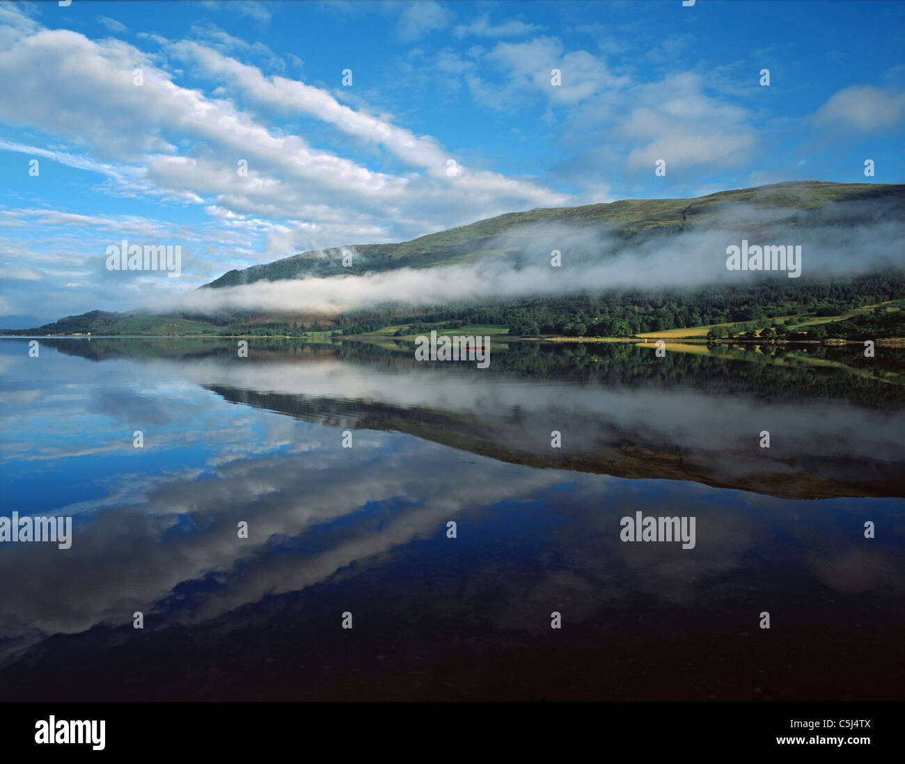 Early morning mist lies along the hill-slopes on the north shore of Loch Leven seen from Invercoe, Glencoe, Scottish - Stock Image