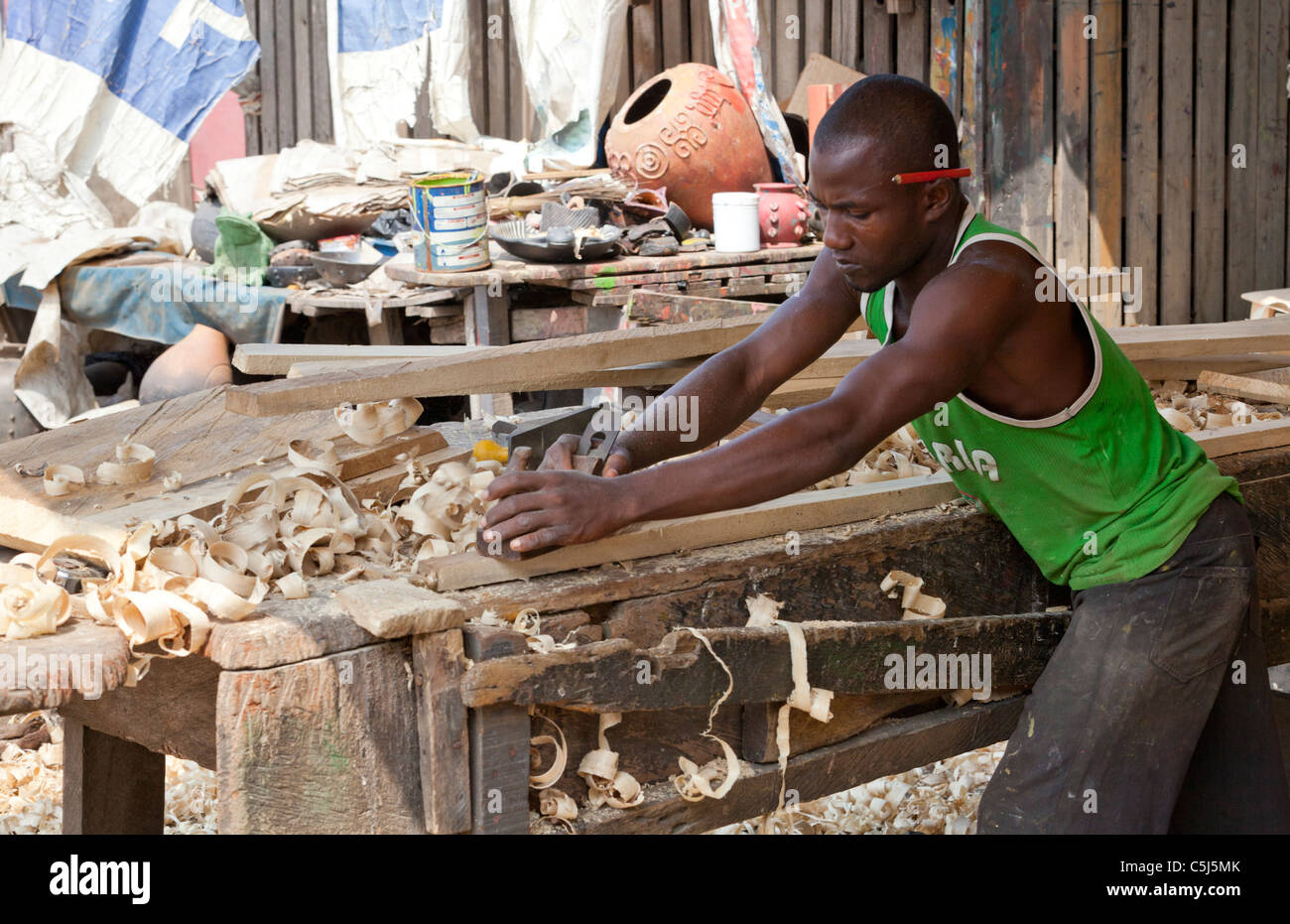 Carpenter planing timber to construct coffin, Accra, Ghana - Stock Image