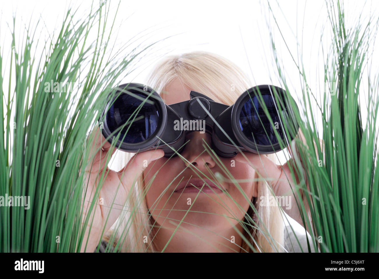 young blond woman with binoculars lying in grass - Stock Image