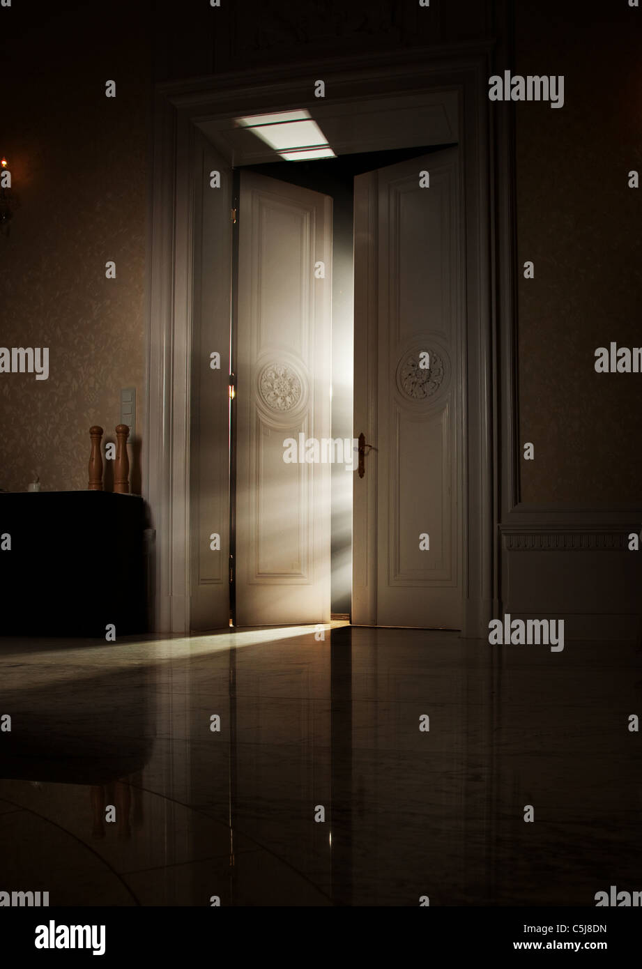 Mysterious rays of light behind door - Stock Image