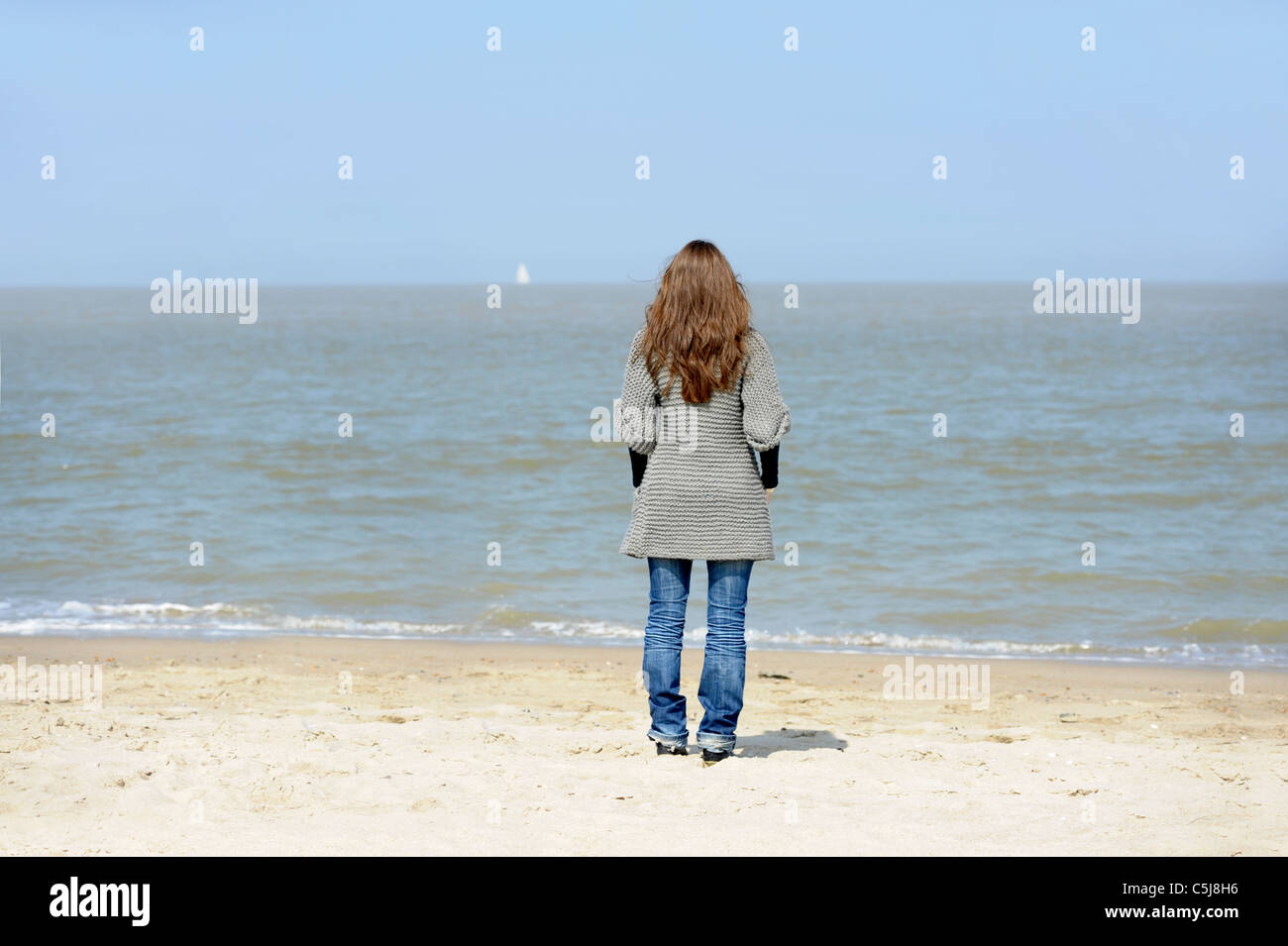 backview of young woman on the beach looking at the ocean - Stock Image