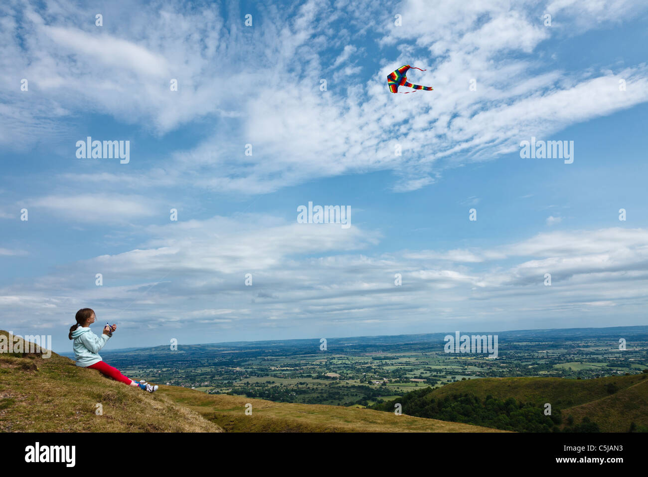 Girl flying kite at British Camp Iron Age hill fort in the Malvern Hills. Stock Photo