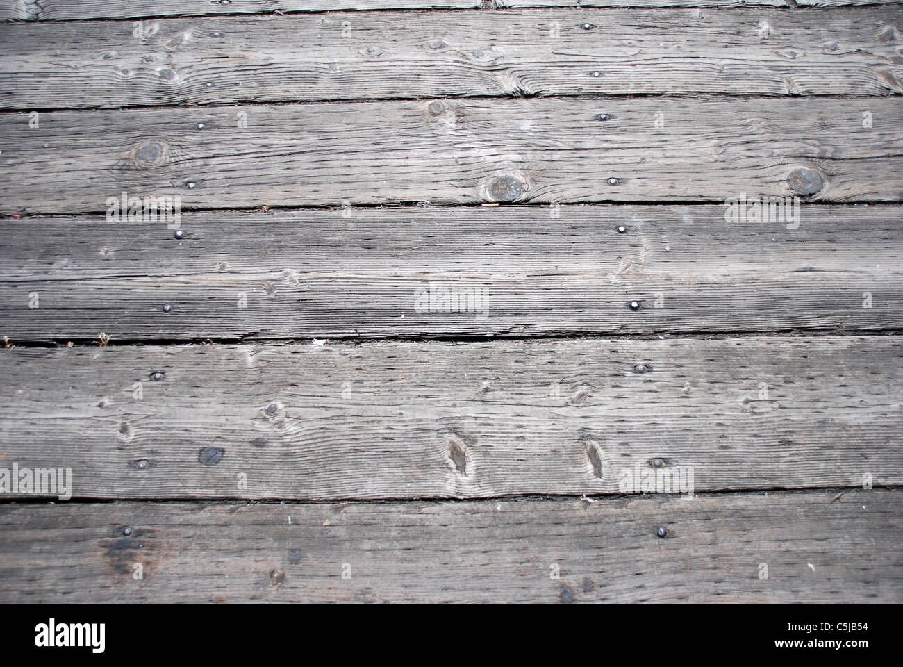 Weatherbeaten wooden walkway laid out in planks in a wooden texture - Stock Image