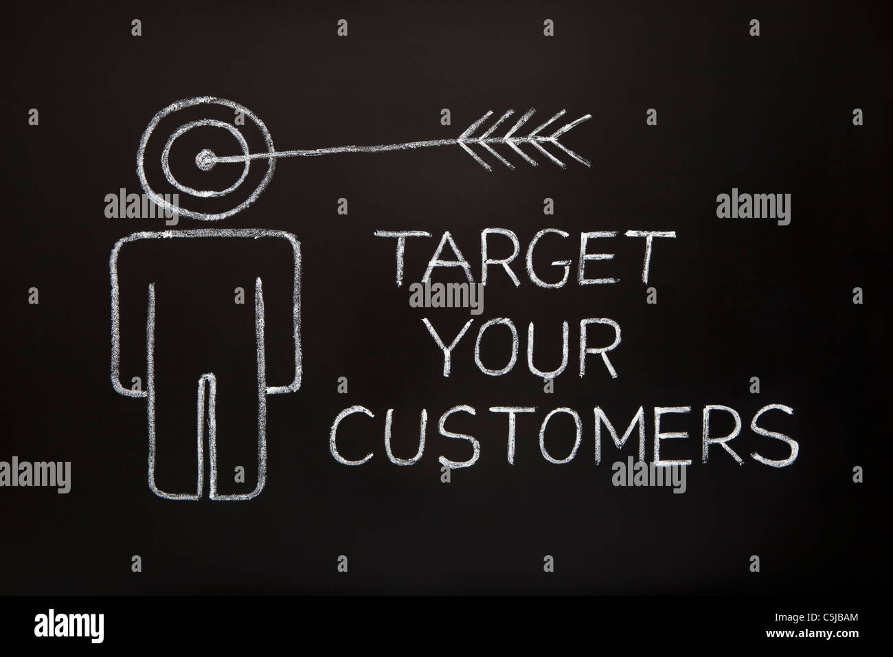 'Target your customers' concept made with white chalk on a blackboard. - Stock Image