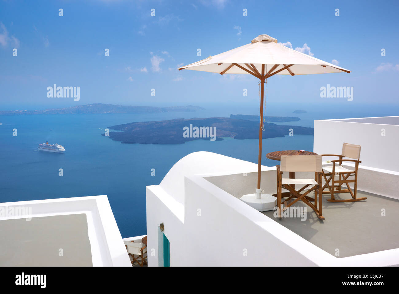Thira (capital of Santorini) - terrace with deck chairs, sun umbrella and blue sea in the background, Santorini - Stock Image