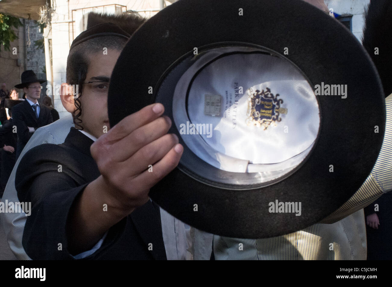 An ultra-Orthodox Jew tries to prevent his photograph being taken during riots to close The Prophets' Road (HaNeviim). Stock Photo