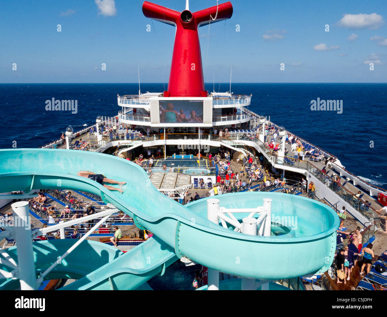 Cruise passengers on deck and water slide on Carnival's Triumph cruise ship in the Gulf of Mexico - Stock Image