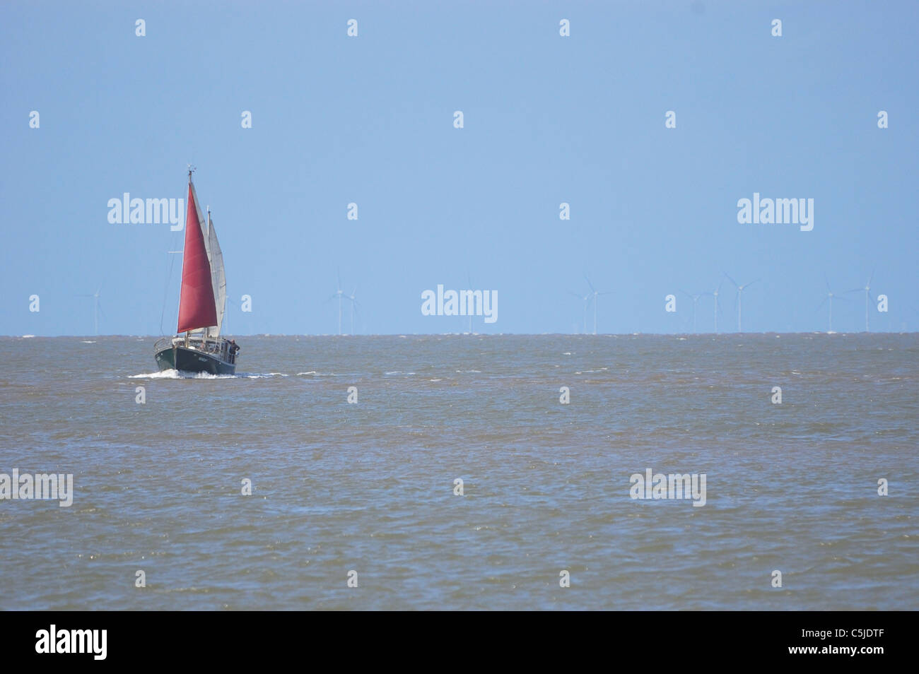 Yacht with red sail approaching mouth of Wyre Estuary Fleetwood - Stock Image